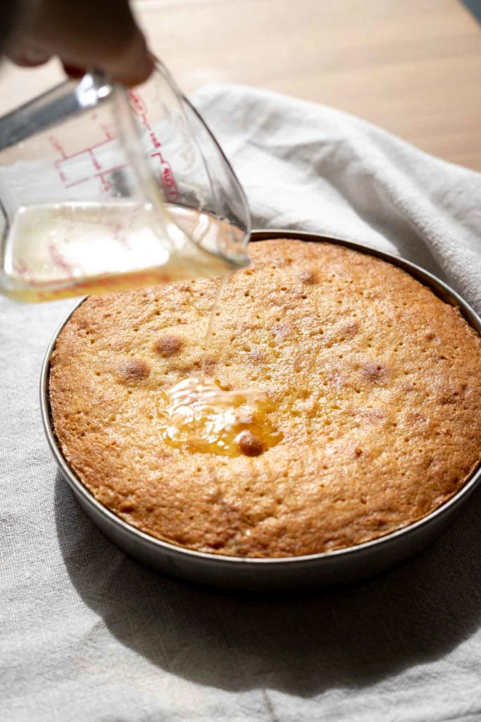 Pouring lemon syrup over single layer lemon cake