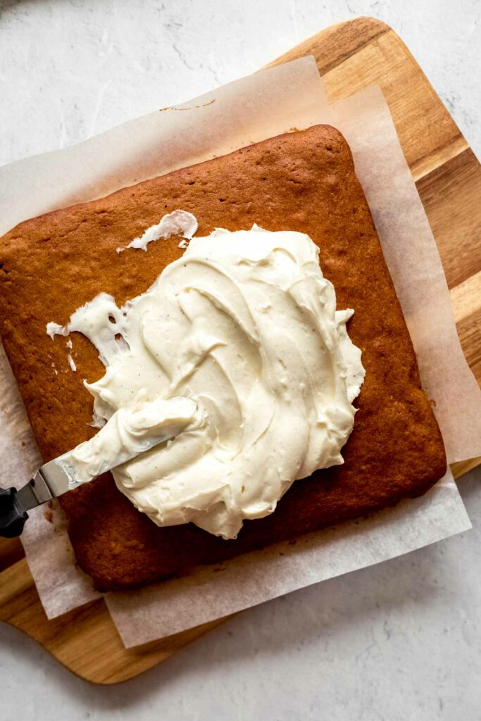 Cream cheese frosting spread on pumpkin cake